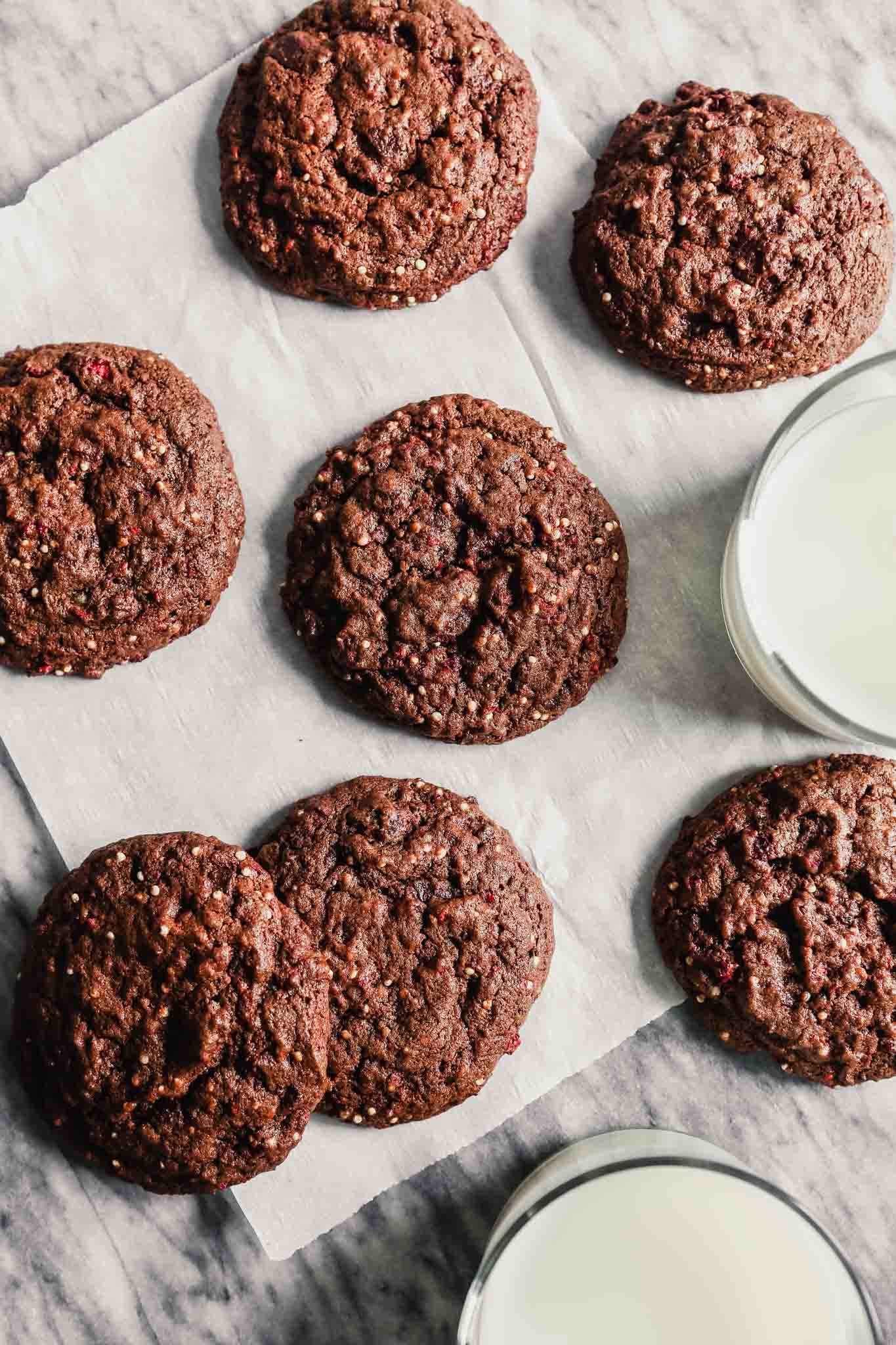 Photograph of chocolate cookies arranged on a piece of parchment paper with glasses of milk set around