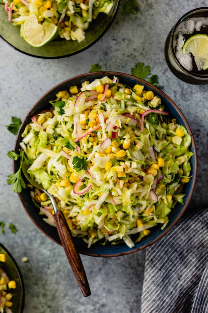 green slaw with sweet corn in a blue bowl