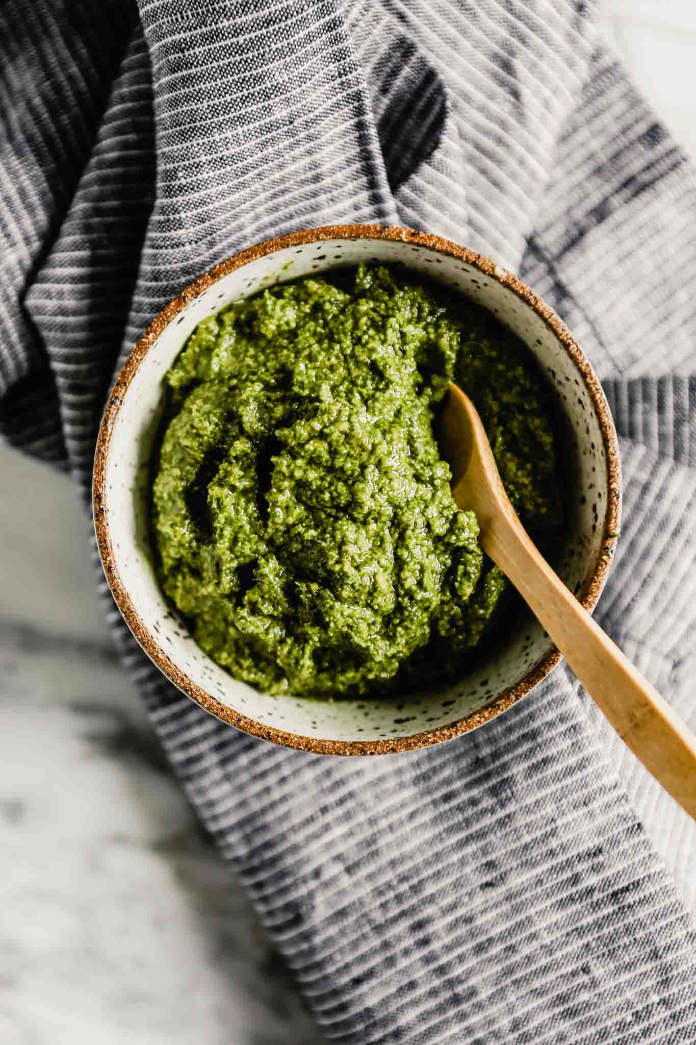Photograph of bright green carrot top pesto in a speckled bowl