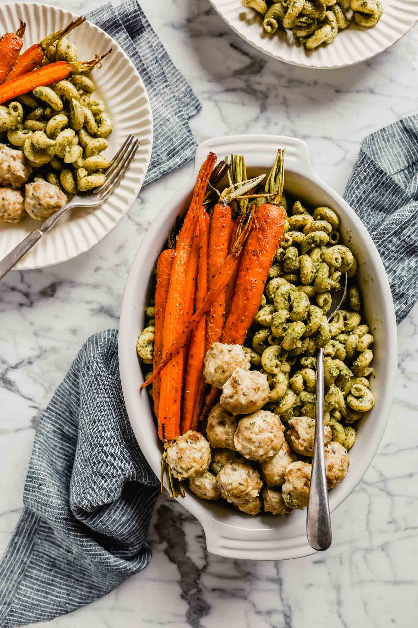 Photograph of a large serving dish filled with pesto pasta, chicken meatballs and roasted carrots