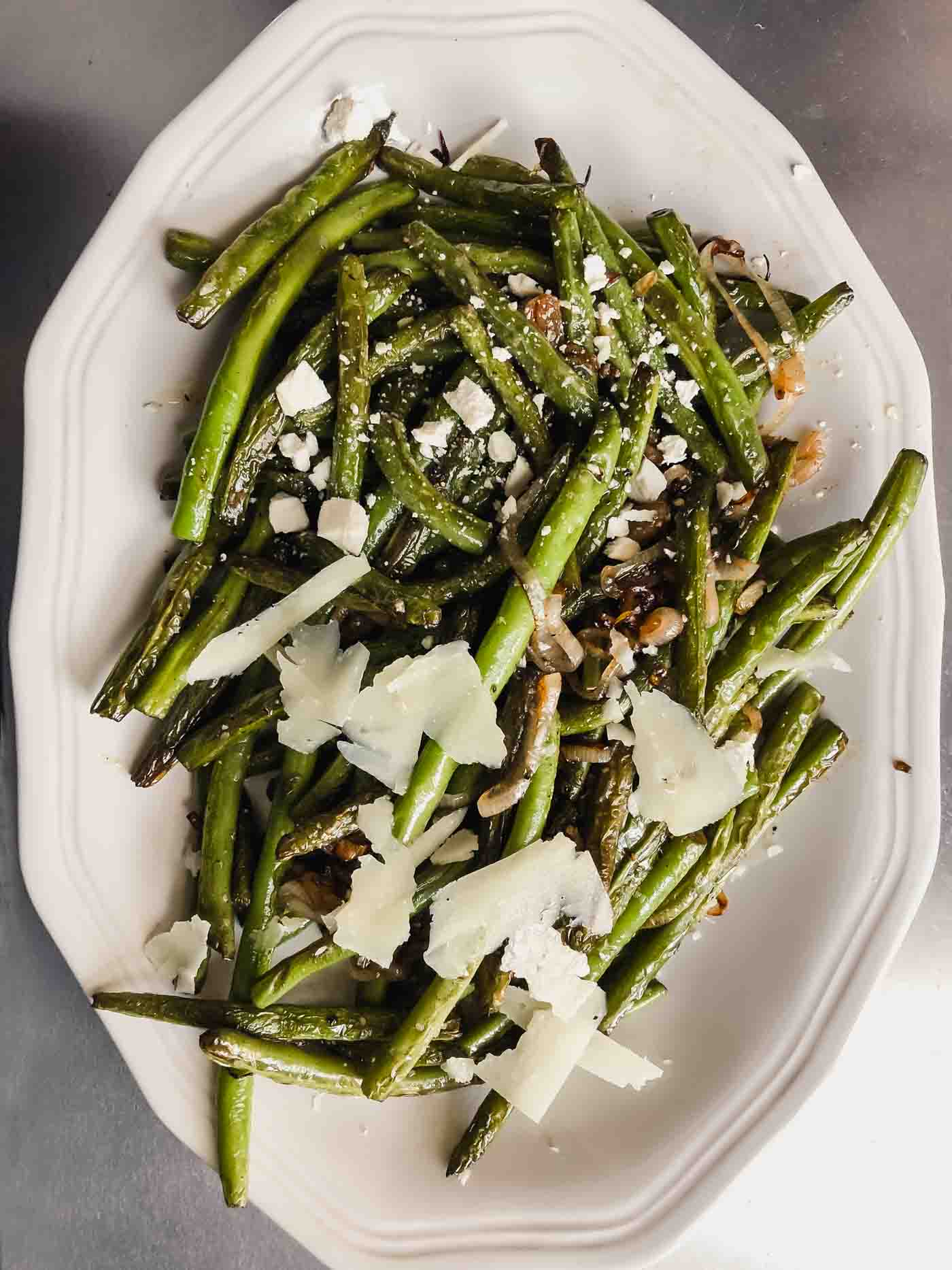 Photograph of green beans on a white oval plate with two different kind of cheeses on different halves