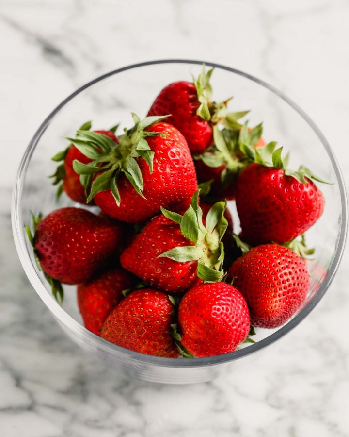 Photograph of fresh strawberries in a glass storage container set on a marble table