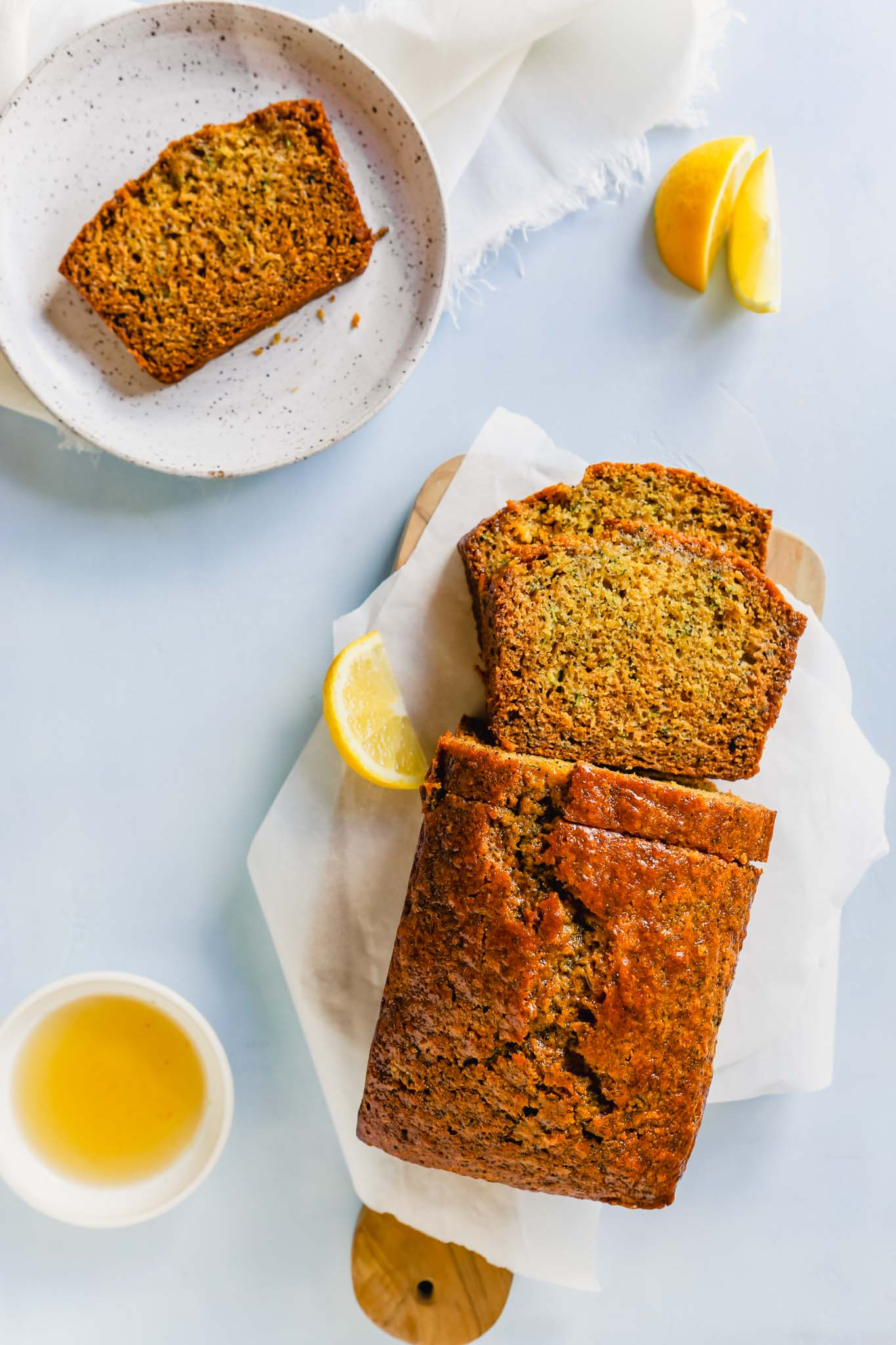 Overhead photo of lemon zucchini bread on a cutting board with a slice on a white plate