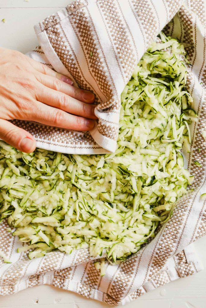 Photograph of shredded zucchini in a kitchen towel
