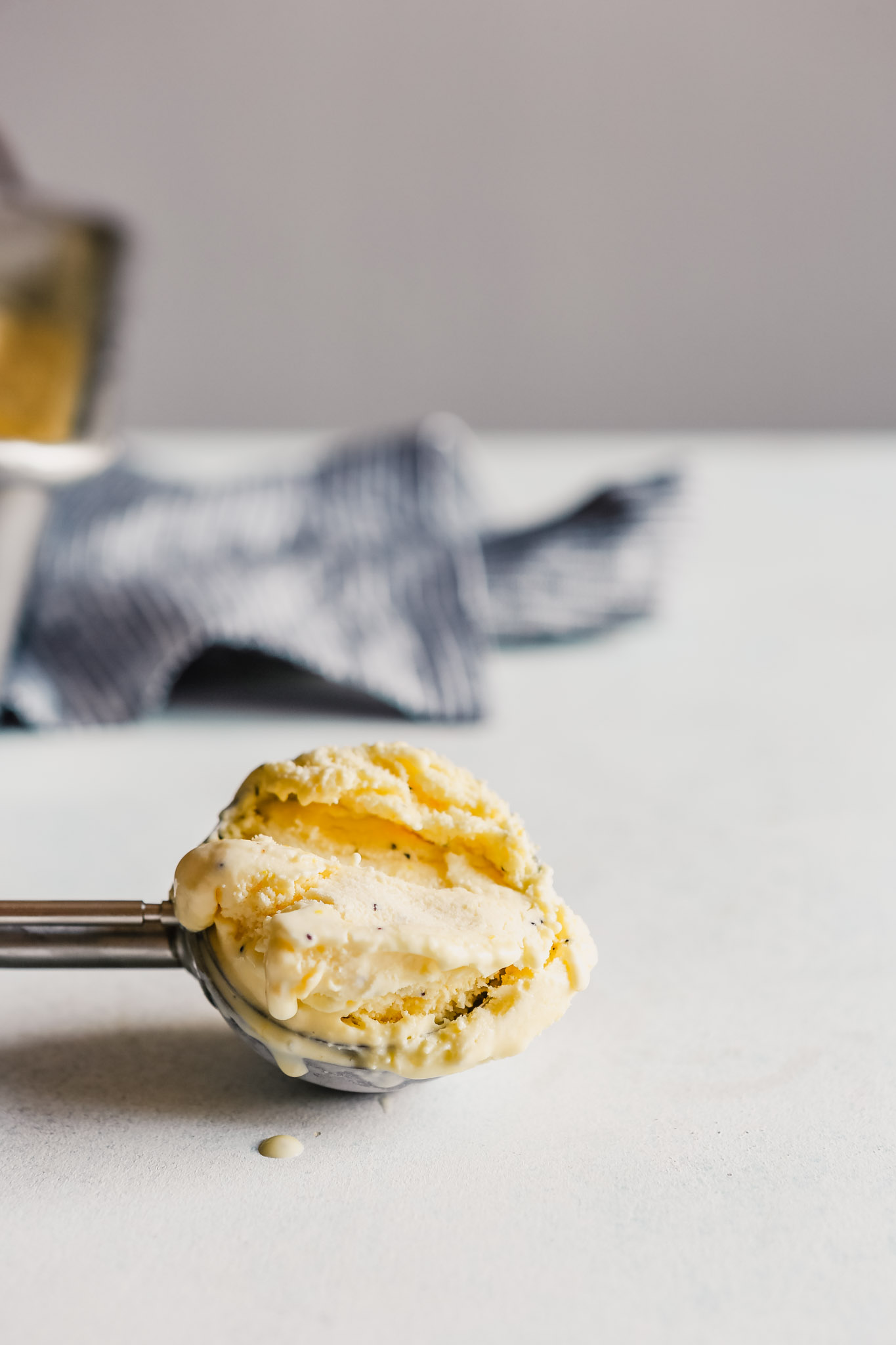 Photograph of a scoop of lemon ice cream in a an ice cream scoop set in a blue table