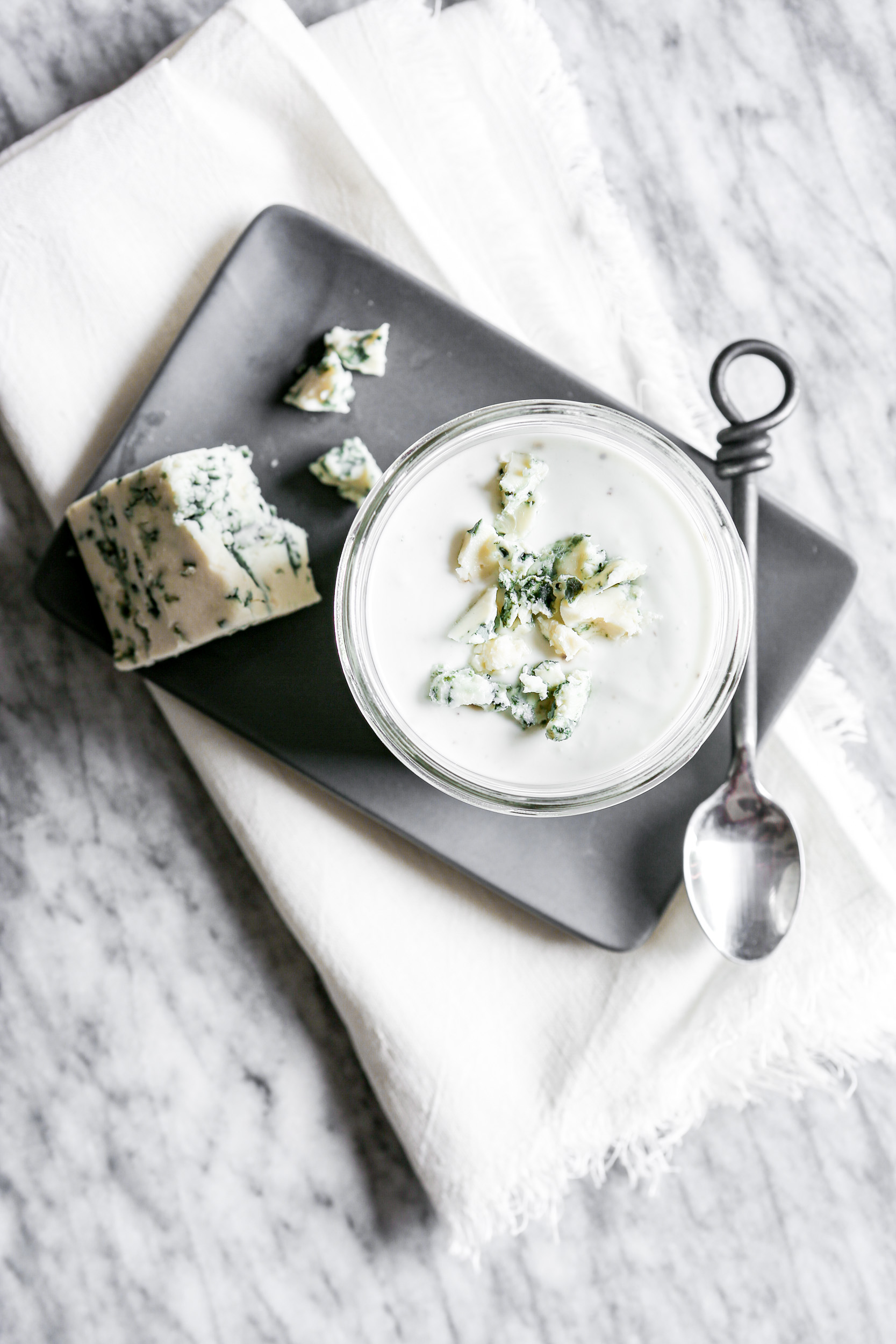 Overhead photograph of blue cheese salad dressing in a glass jar set on a gray plate on a marble table.