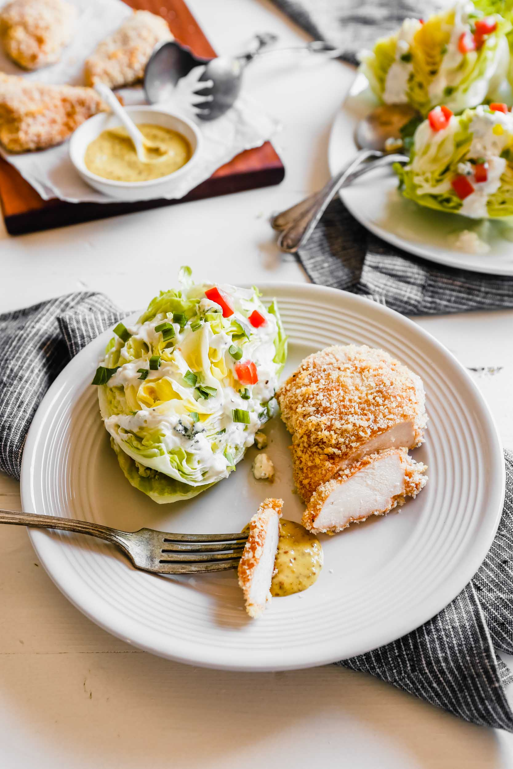 Photograph of oven fried chicken breast being cut on a plate with a wedge salad