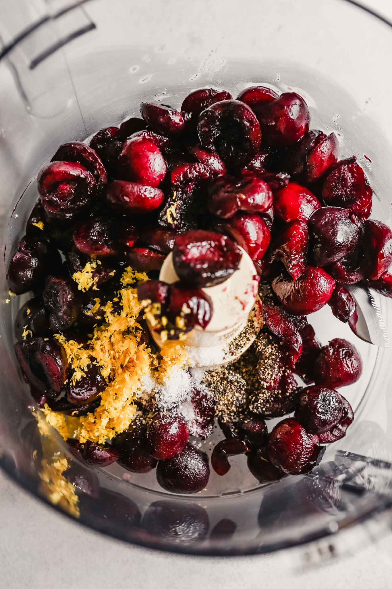 photo of cherries in a food processor with lemon zest, salt and pepper