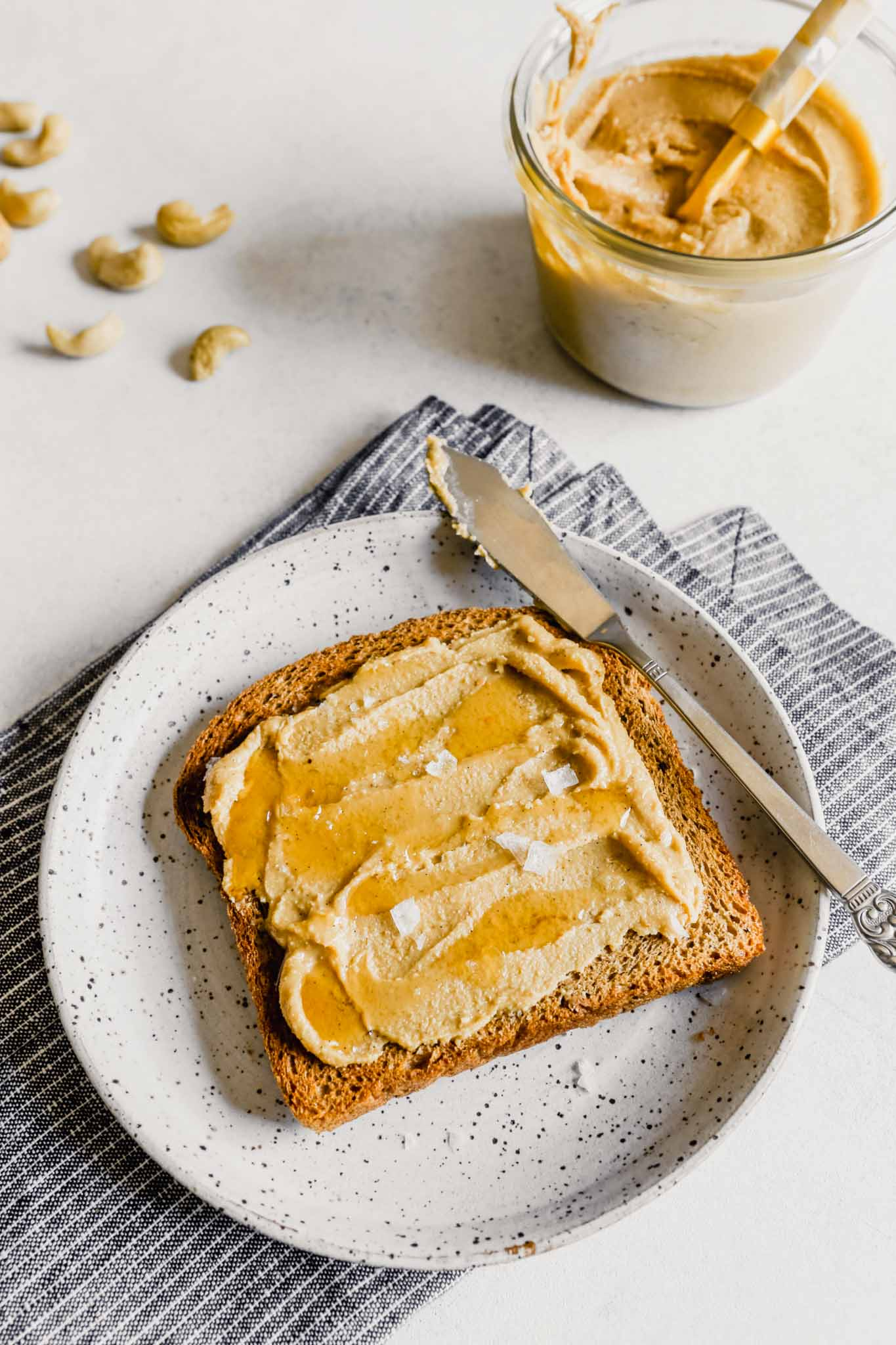 Photo of cashew butter spread onto a piece of toast with honey and sea salt