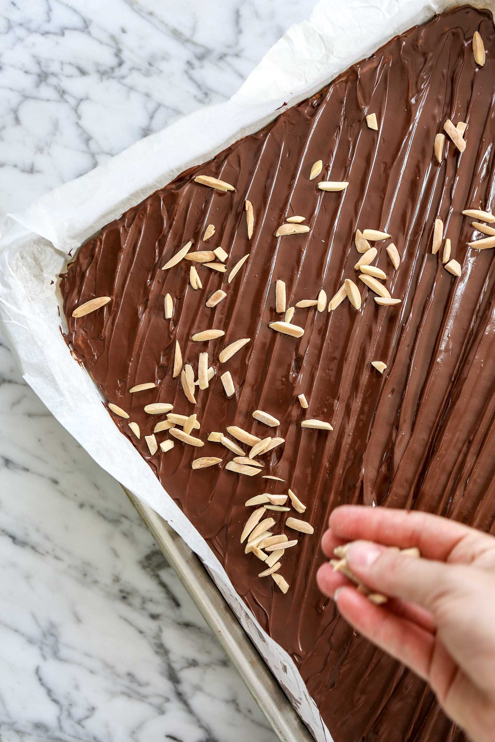 photo of almonds being sprinkled over chocolate layer on cookie bar