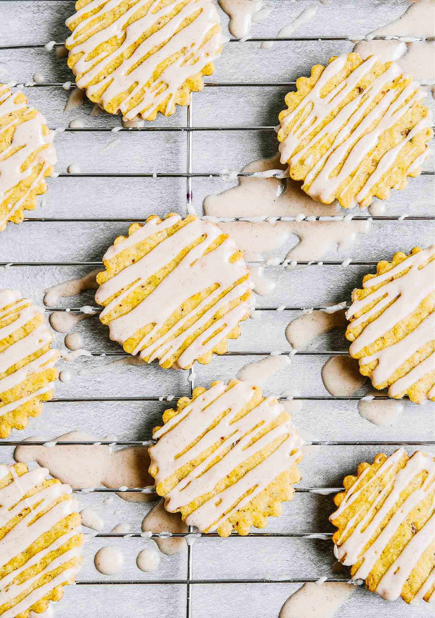 Iced pumpkin cookies set on a wire rack on a concrete table.