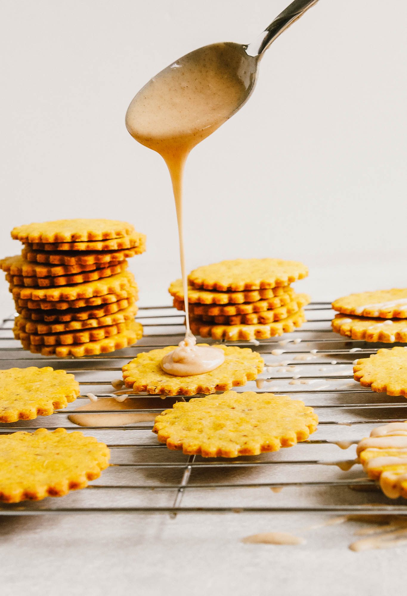 Pumpkin cookies set and stacked on a wire rack getting iced
