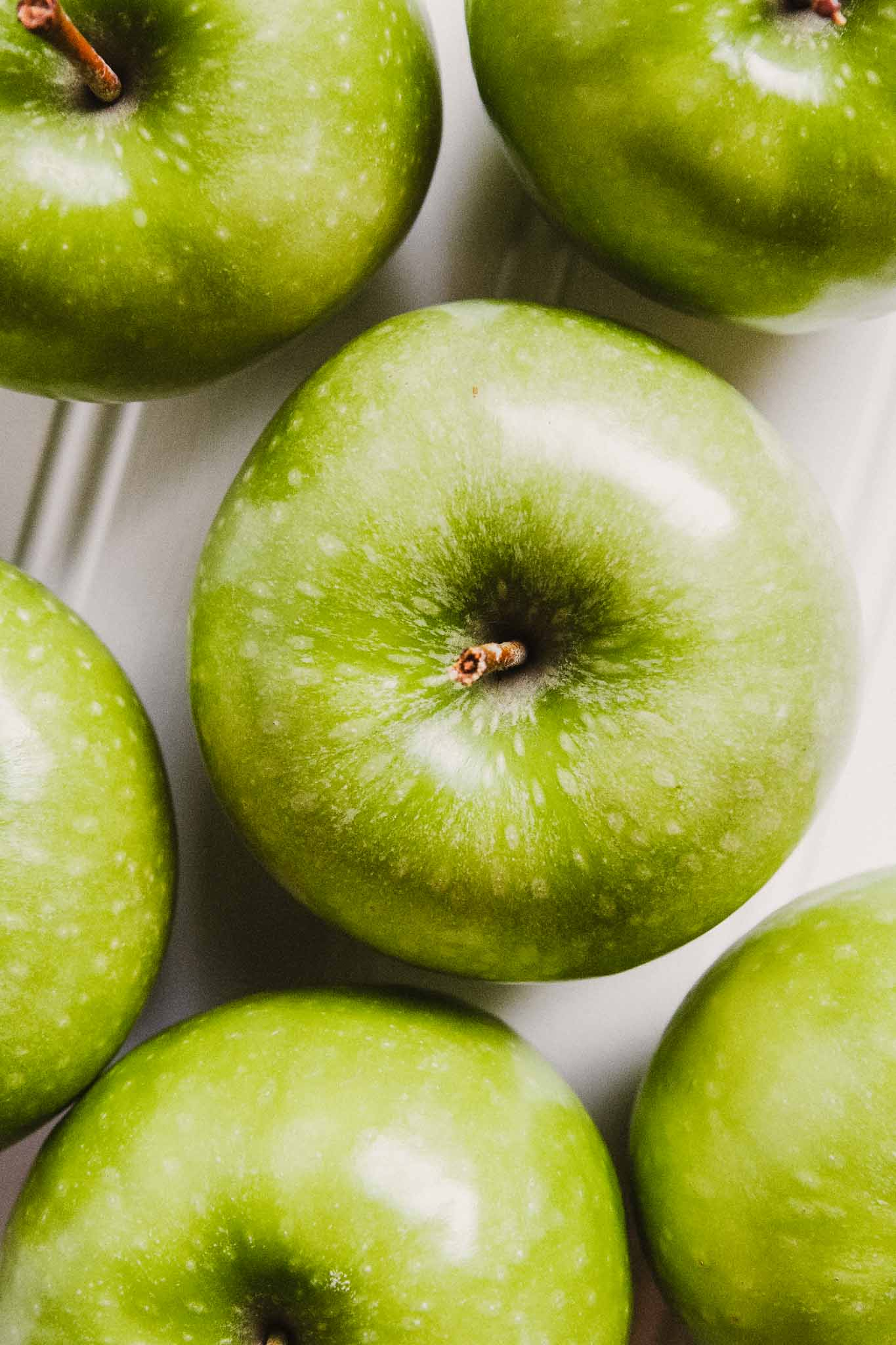 overhead photograph of green apples set on a white table