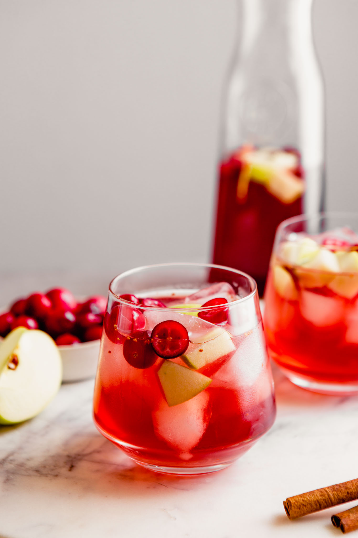 Photograph of two glasses of rose sangria set on a marble platter with a pitcher of sangria in the background.