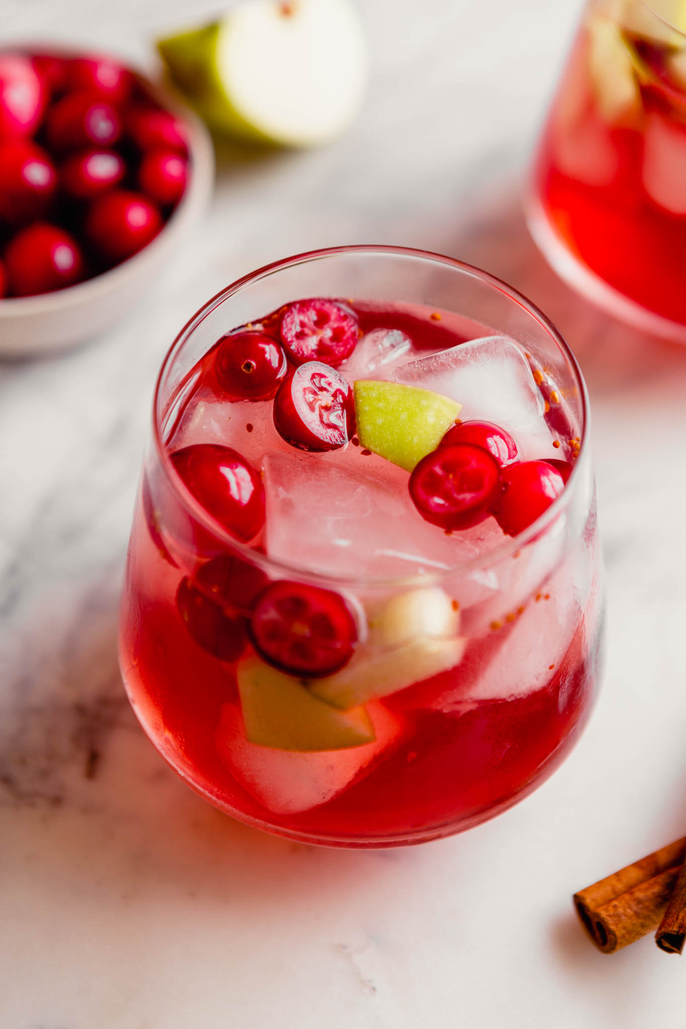 45-degree photograph of a fall sangria, featuring fresh cranberries and apple chunks, set on a marble platter.