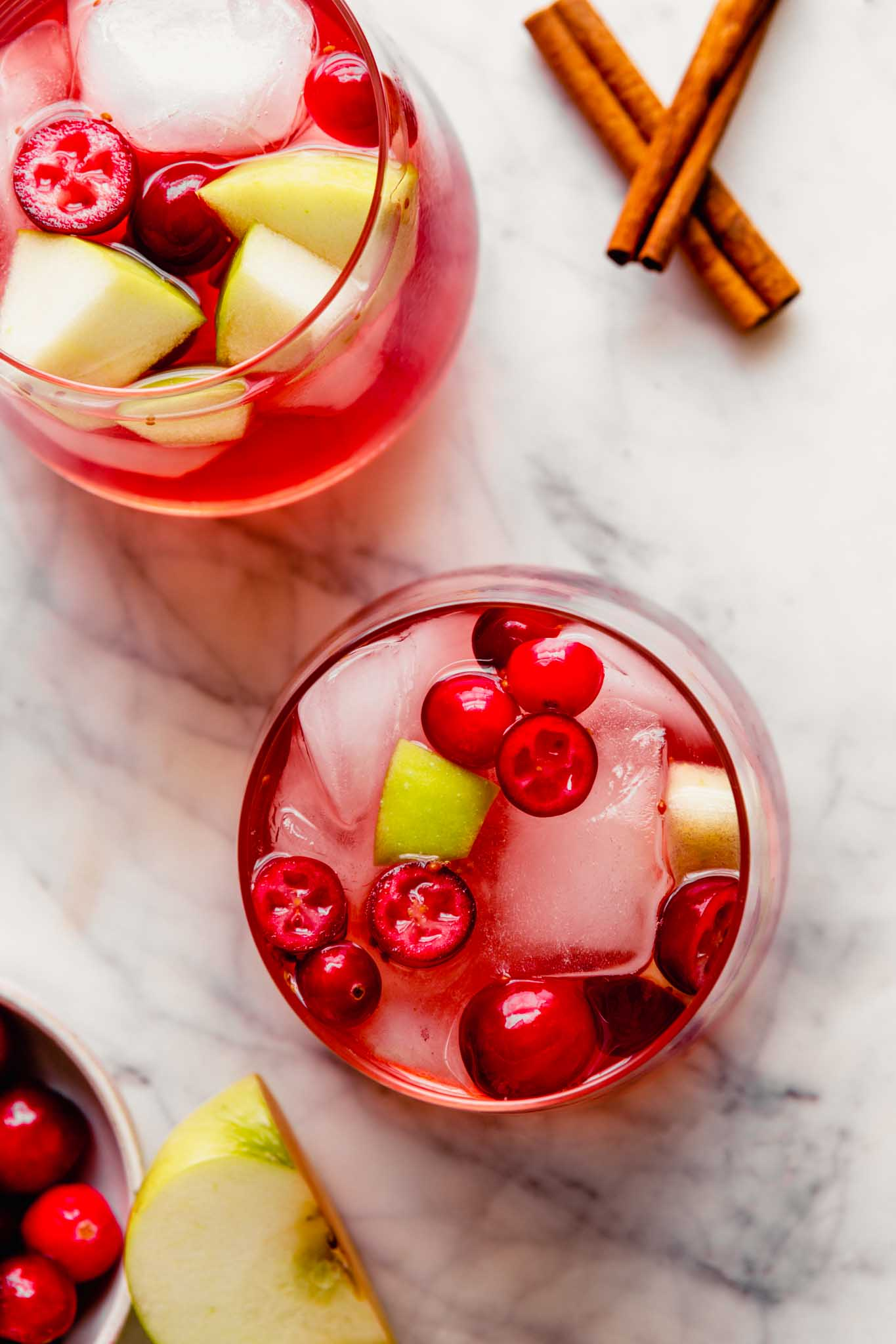 Overhead photograph of a fall sangria, featuring fresh cranberries and apple chunks, set on a marble platter.