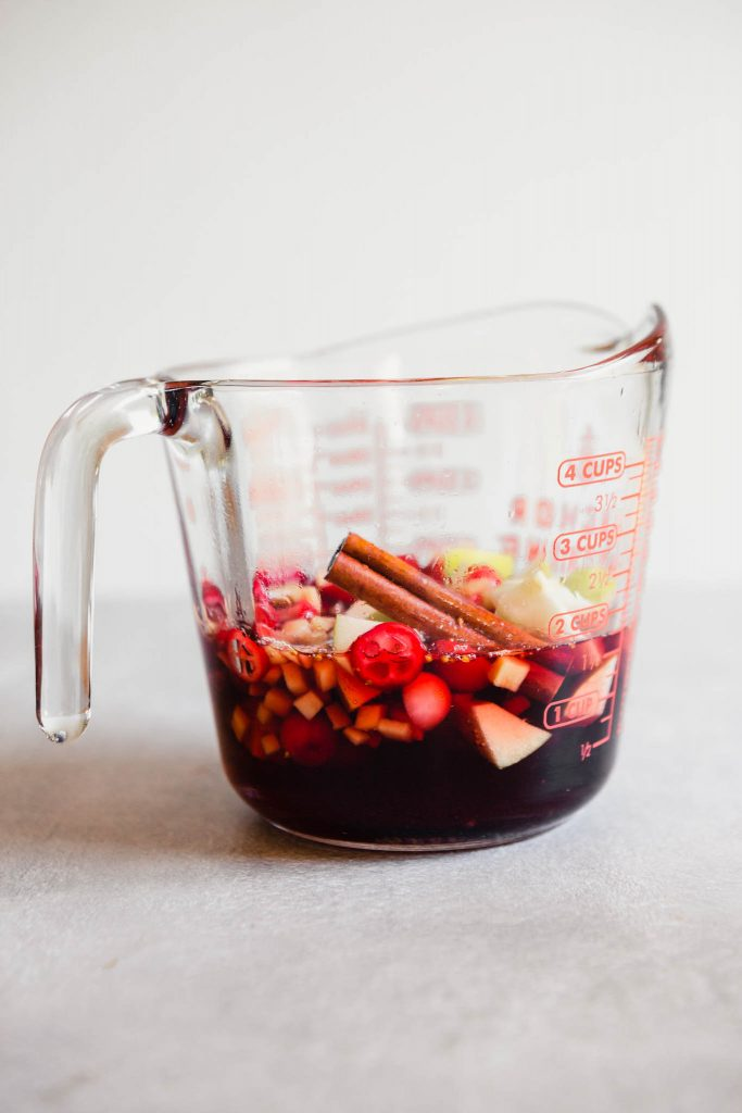 Photograph of a flavored cranberry simple syrup in a glass measuring cup.