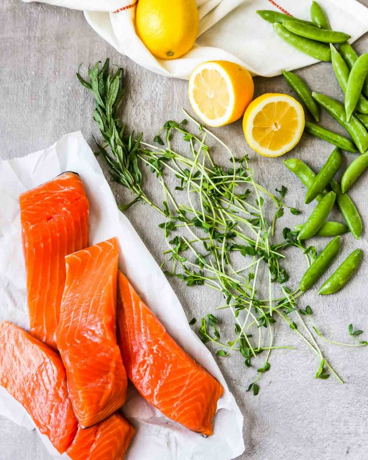 Overhead photo of fresh salmon filets stacked on a white paper with lemon, peas and herbs scattered around them.