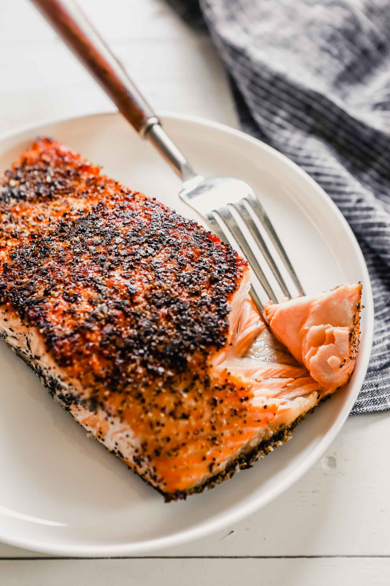 Close up photo of crispy pan seared salmon with skin set on a white plate with a fork taking a large chunk out of it