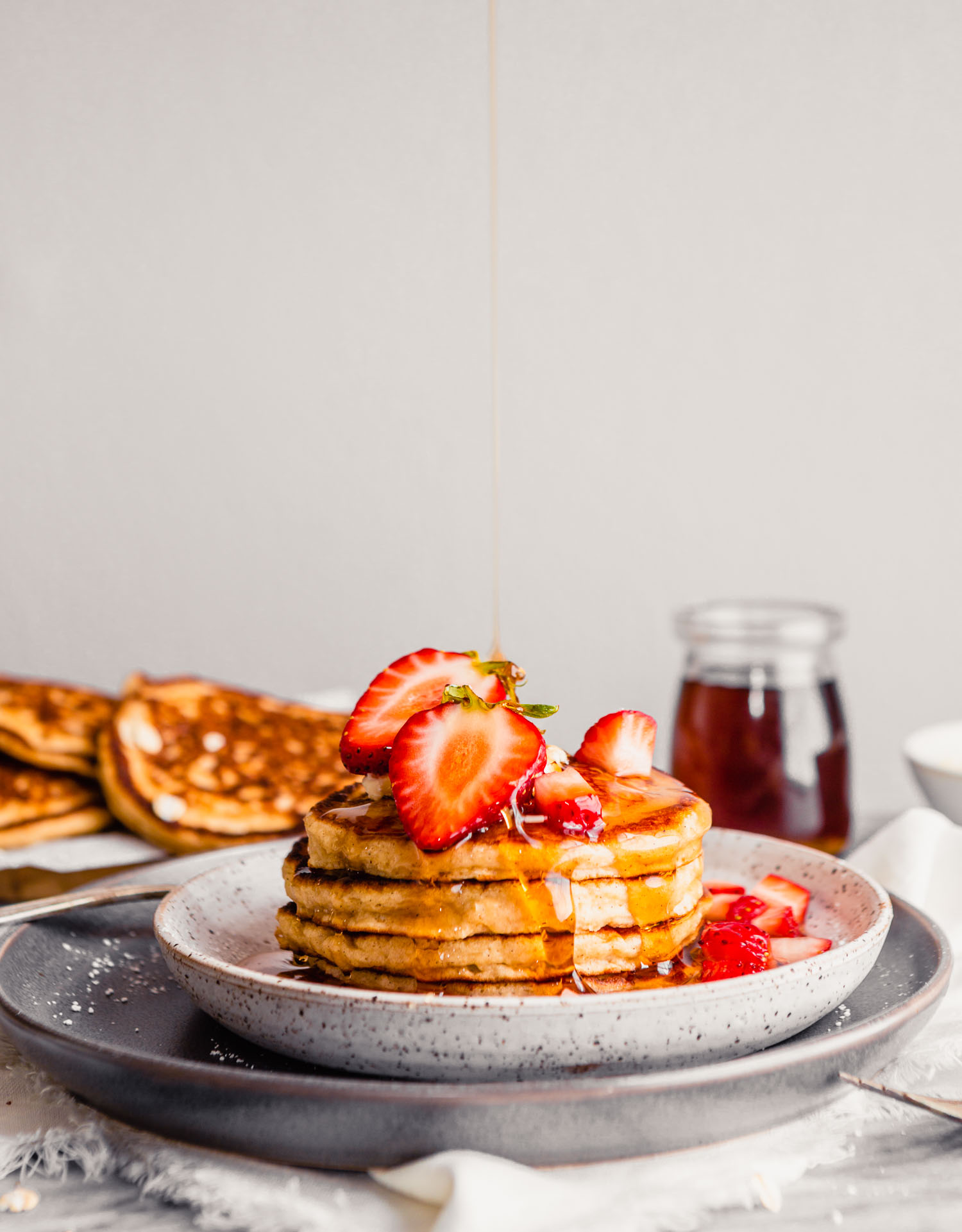 Photo of toasted oat pancakes stacked on a plate topped with butter, maple syrup and strawberries