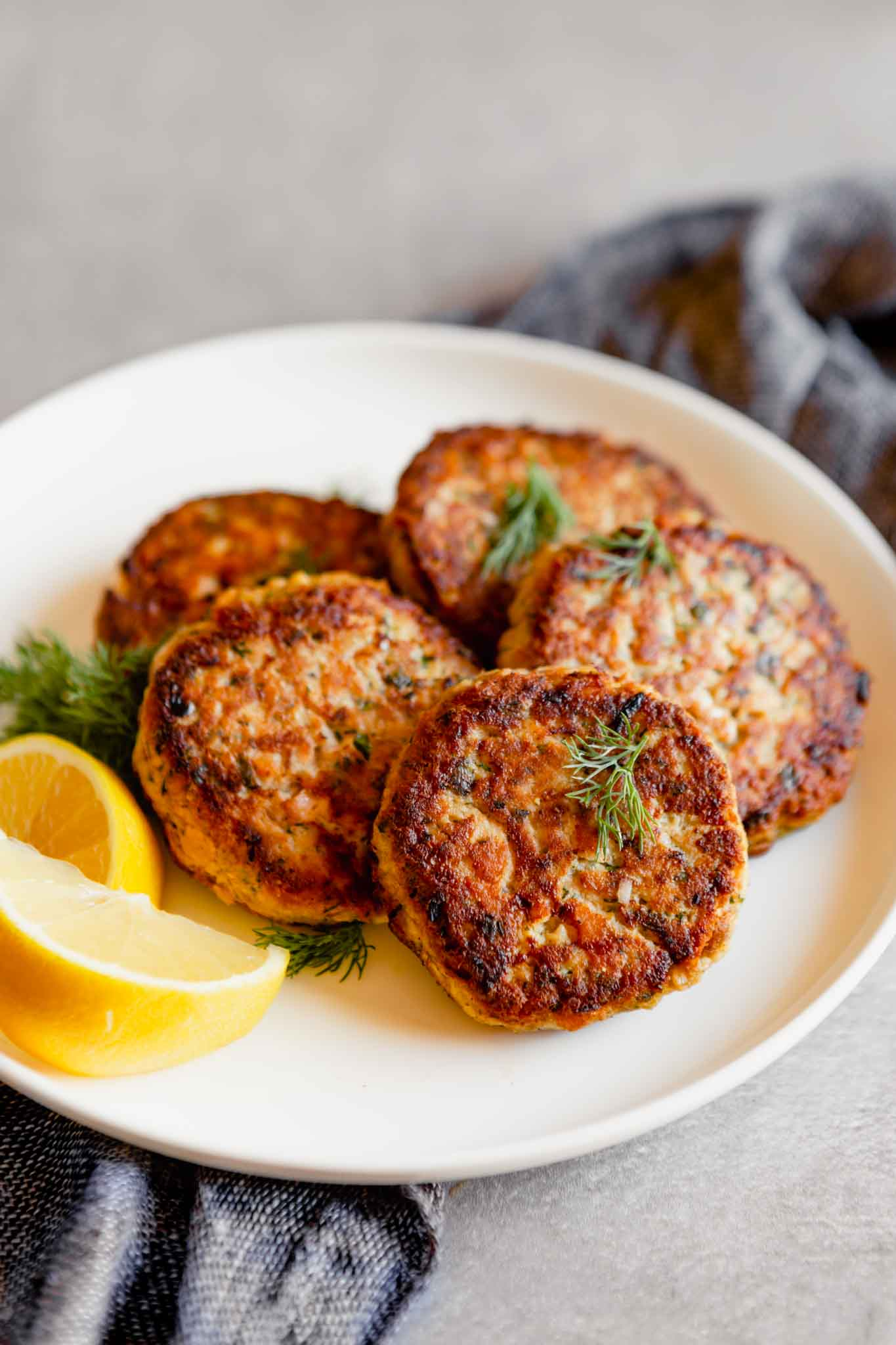 Photo of salmon cakes stacked on a white plate with lemon slices on a gray table.