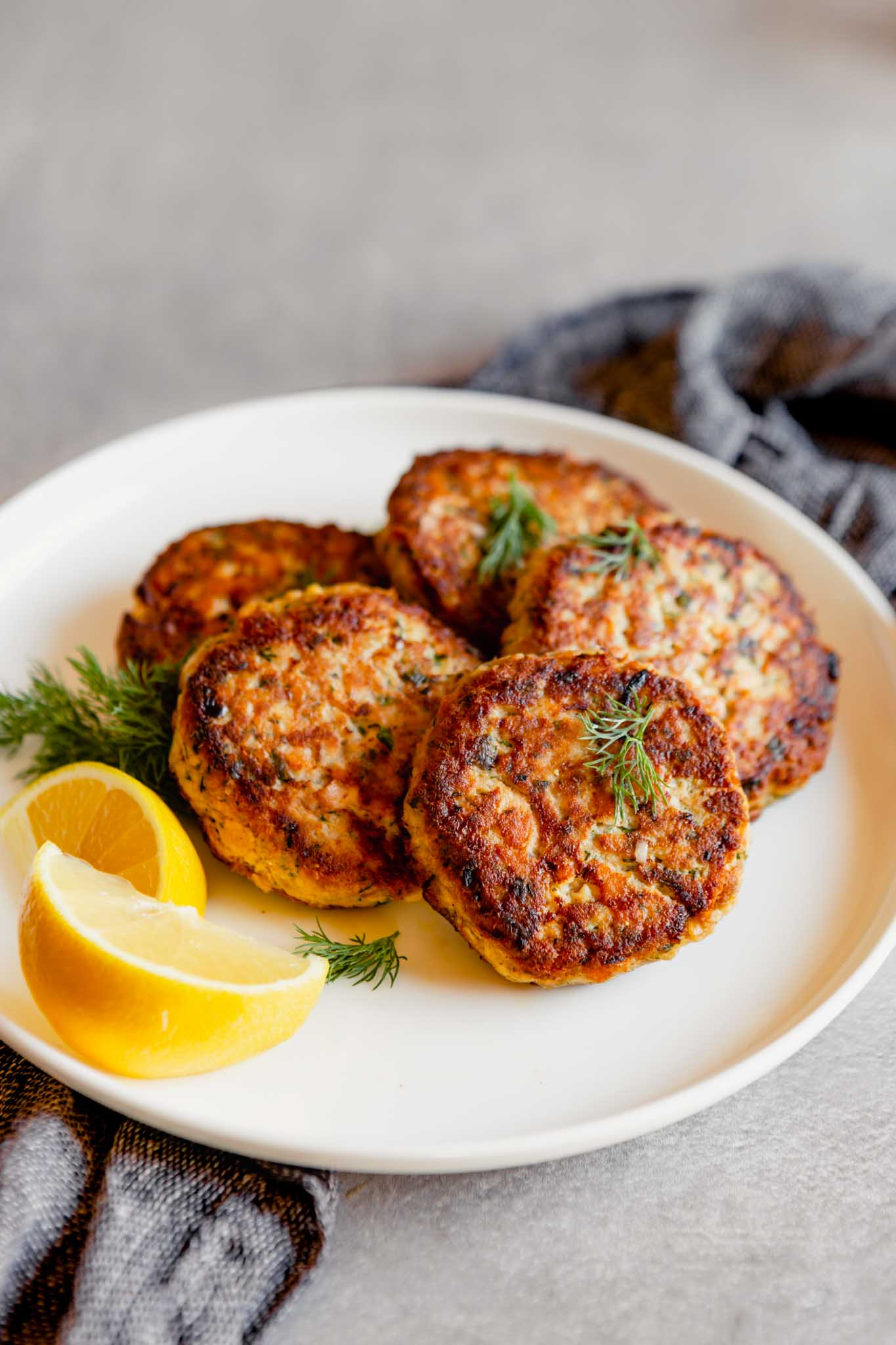 Photo of salmon cakes stacked on a white plate with lemon slices on a gray table with a blue napkin.