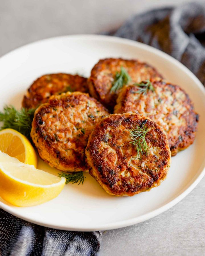 Close up photo of salmon cakes stacked on a white plate with lemon slices on a gray table with a blue napkin.