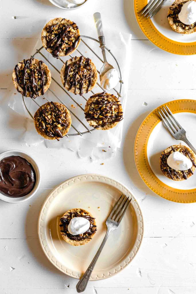 Overhead image of mini pecan pies (pecan tassies) arranged on a cooling rack and a varity of gold-colored plates on a white table