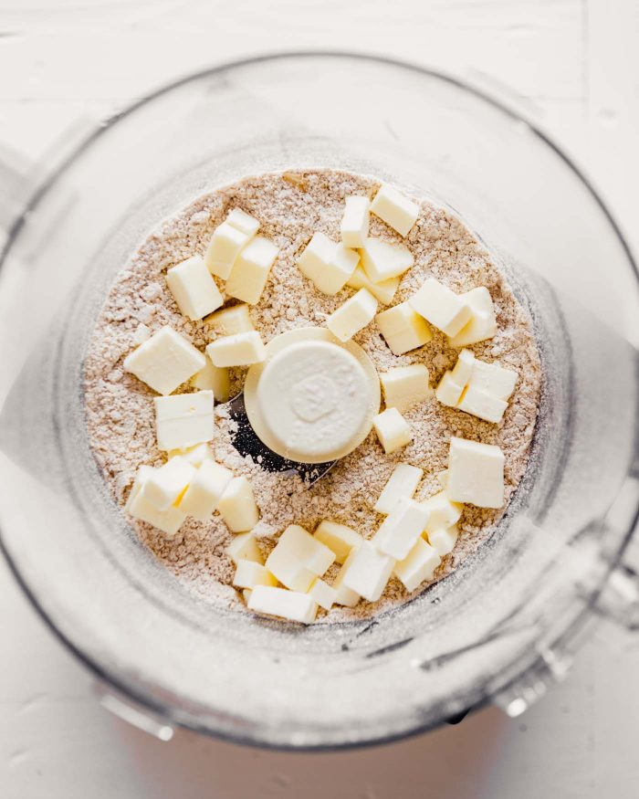 overhead photo of diced butter scattered over top of dry ingredients in a food processor