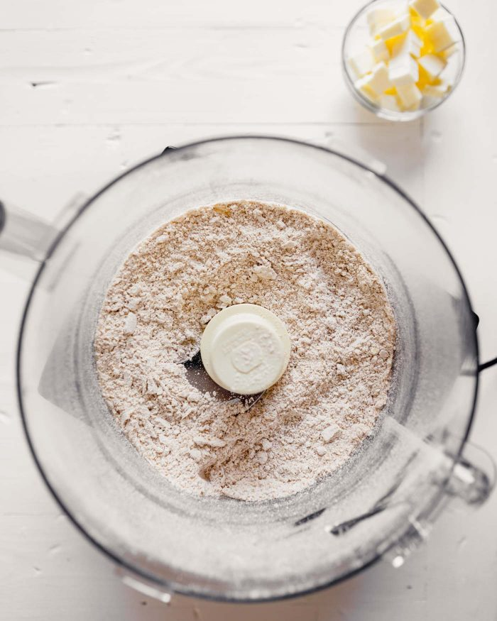 Overhead image of dry ingredients in a food processor with butter off to the side