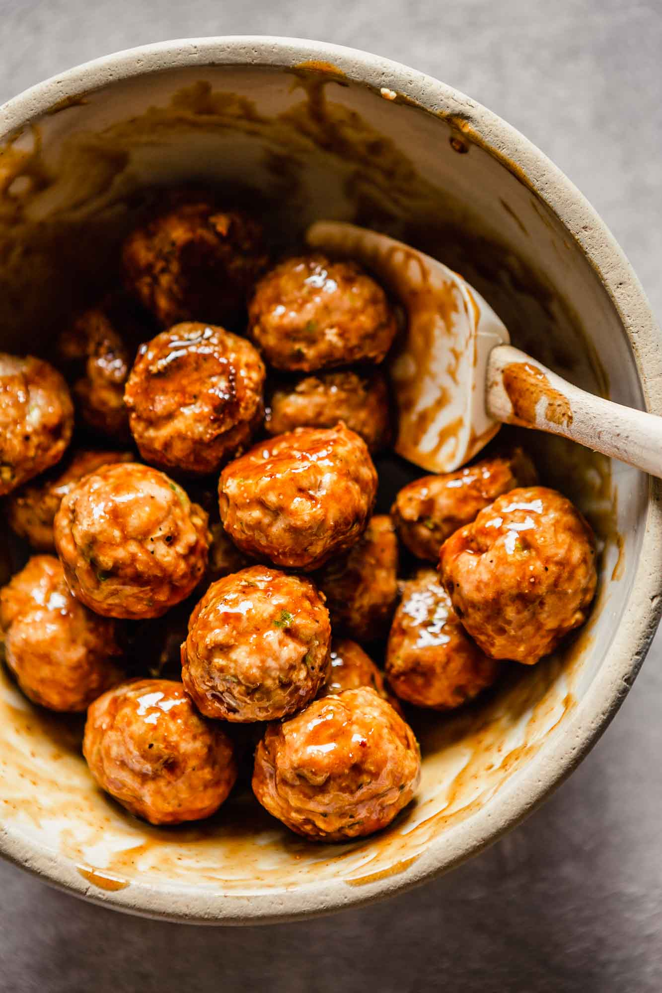 meatballs in a bowl coated in a orange-brown glaze