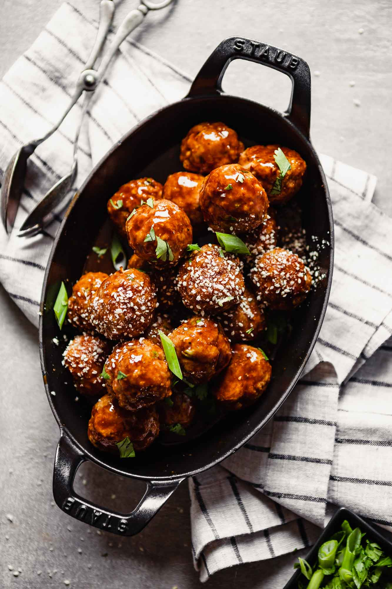Overhead image of glazed turkey meatballs piled into an oval baking dish topped with panko and scallions