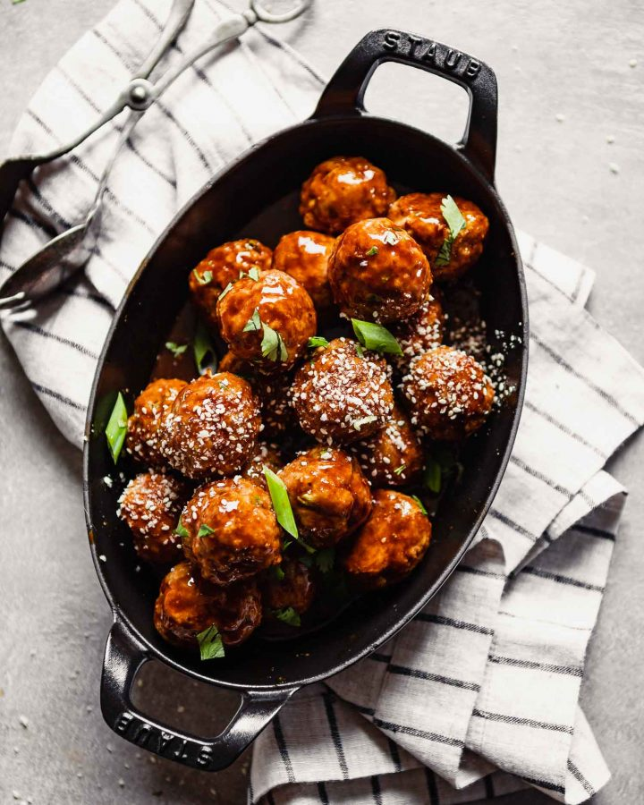 Overhead image of glazed turkey meatballs piled into an oval baking dish set on a stripped napkin.