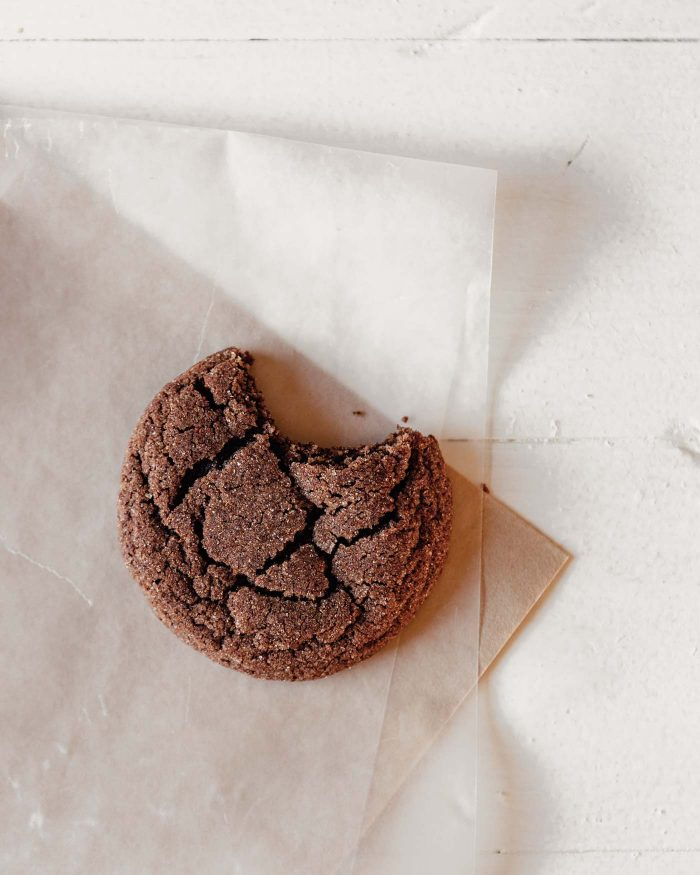 overhead photo of a single chocolate cookie set on parchment paper with a bite taken out of it