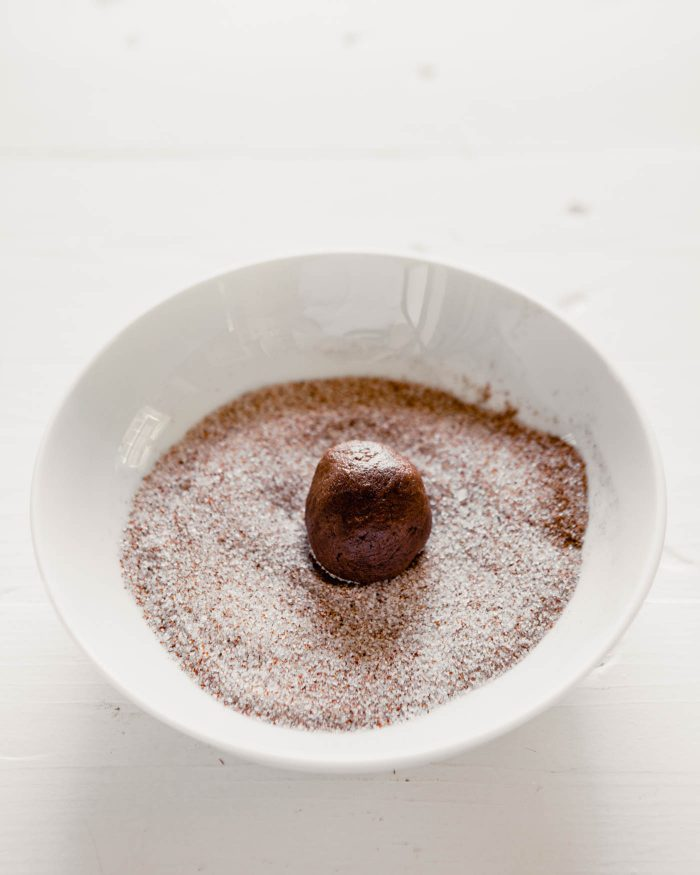 photo of a ball of cookie dough getting rolled in a spiced sugar mixture