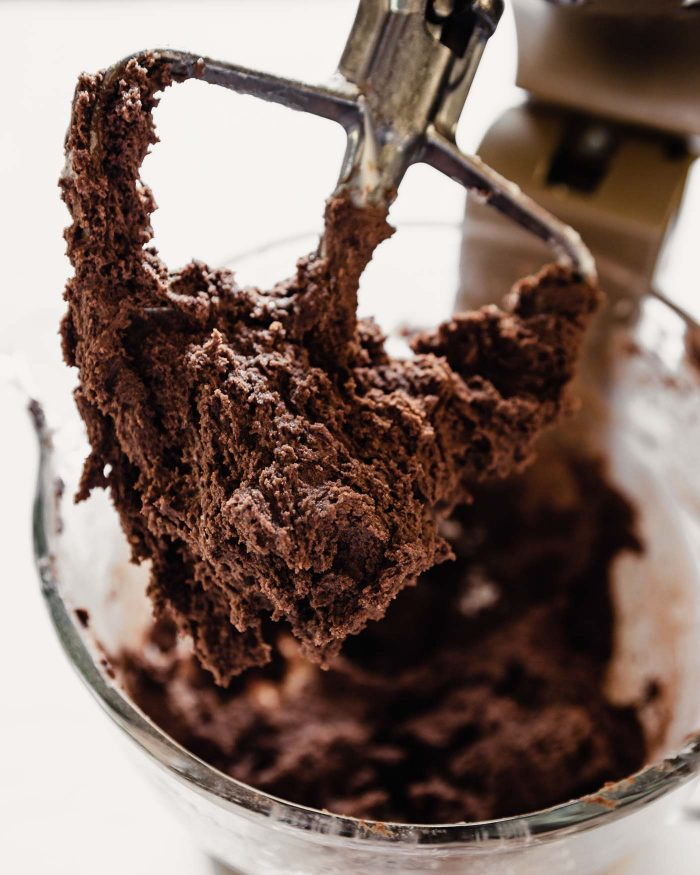 chocolate cookie dough in a stand mixer and on a paddle attachment