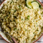 overhead image of brown rice with chopped cilantro and lime wedges in a shallow bowl