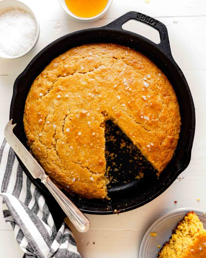 Overhead image of healthy cornbread in a cast iron skillet set on a wooden white table with a striped napkin and a knife