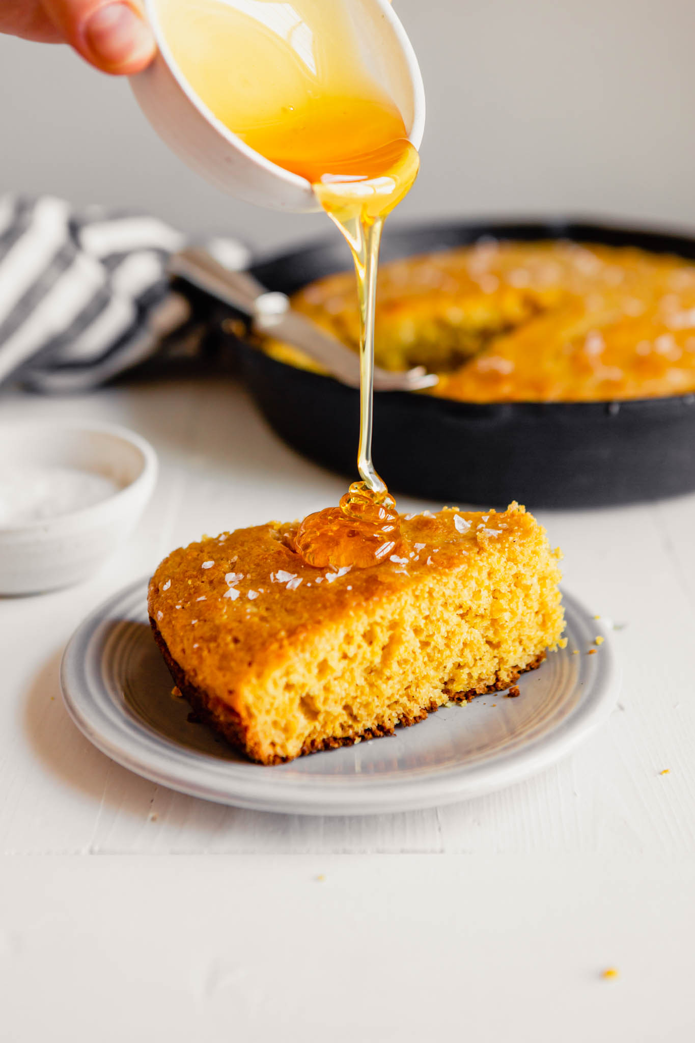 Side angle of a wedge of healthy cornbread with honey being drizzled over it