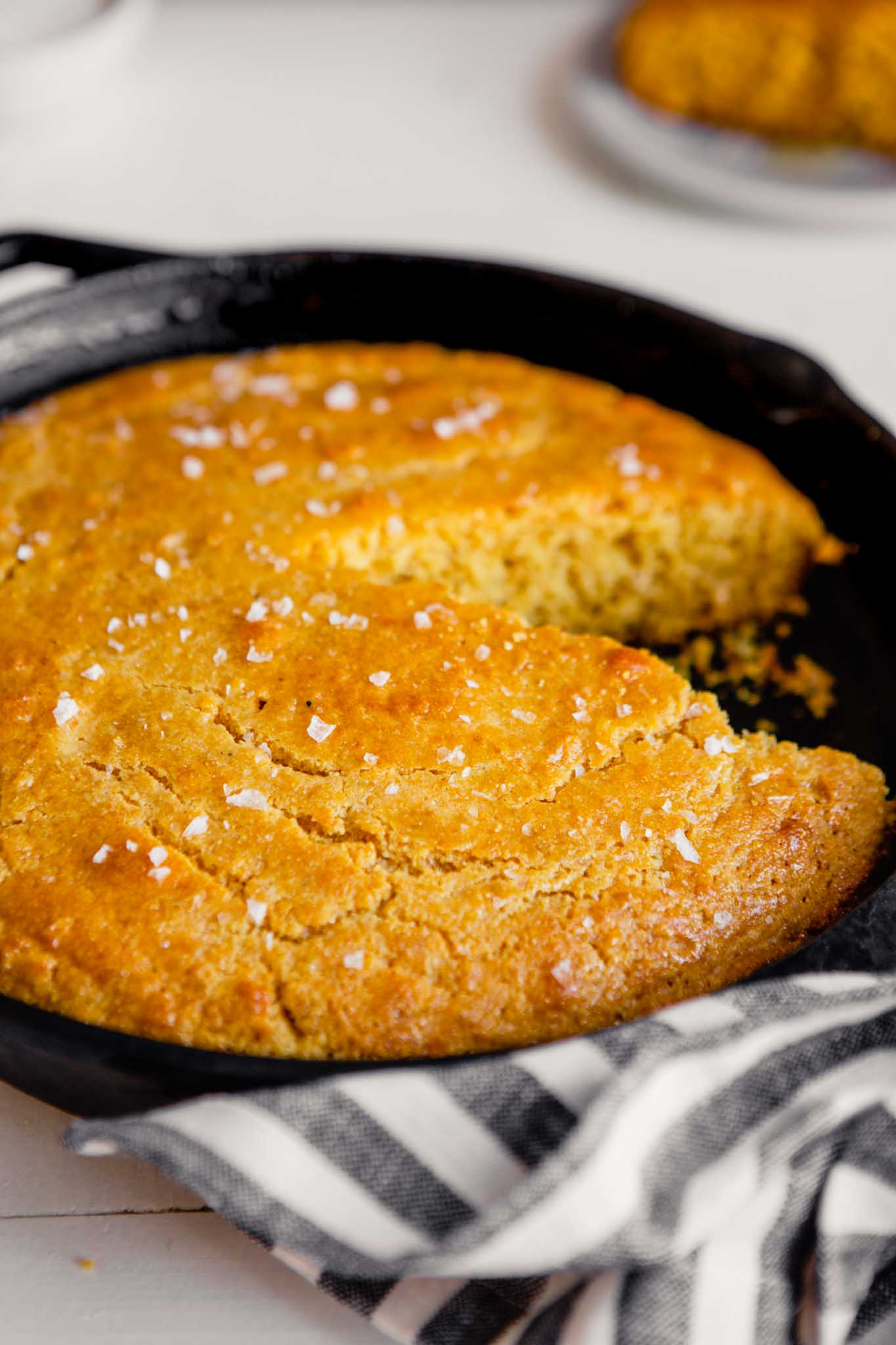 Side angle of cornbread in a cast iron skillet with a piece taken out