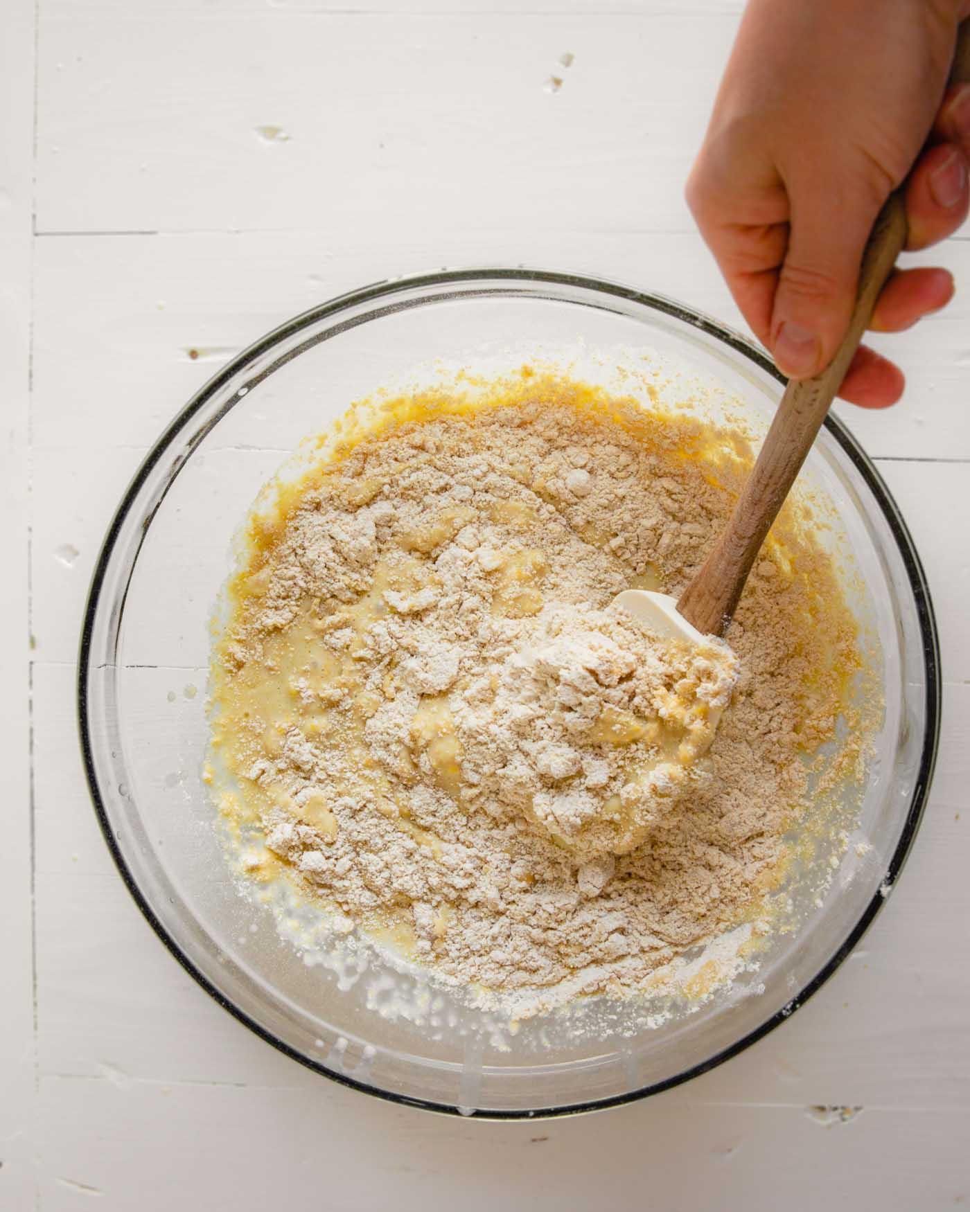 Overhead photo of wet ingredients being mixed into dry ingredients for healthy cornbread