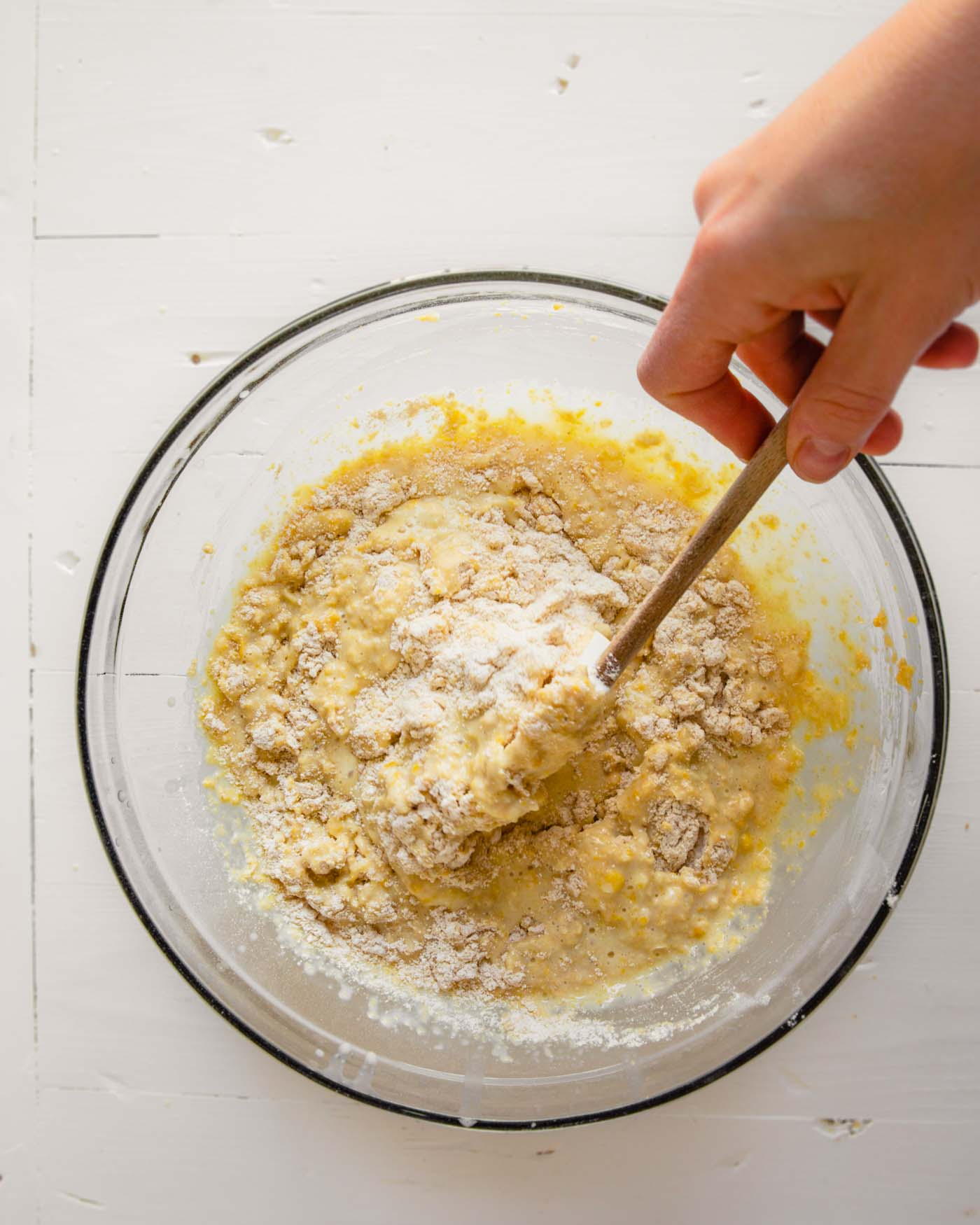 Overhead photo of batter being mixed together in a glass bowl set on a white table