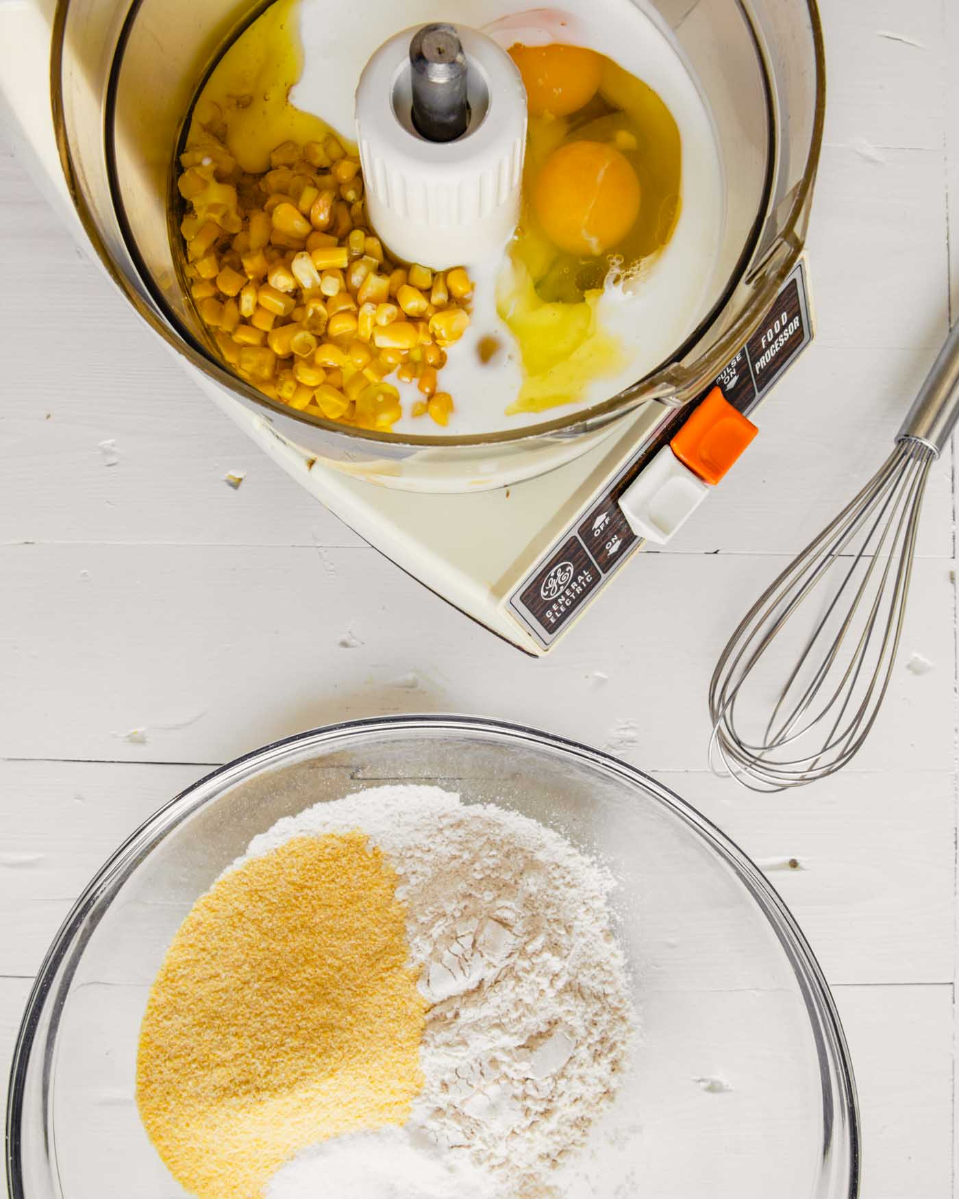 Overhead image of ingredients for a healthy cornbread arranged on a white wooden table