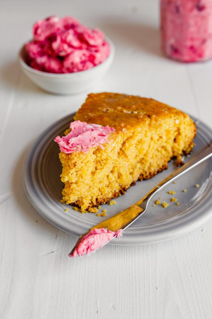 photo of a slice of cornbread with cranberry butter spread over top of it