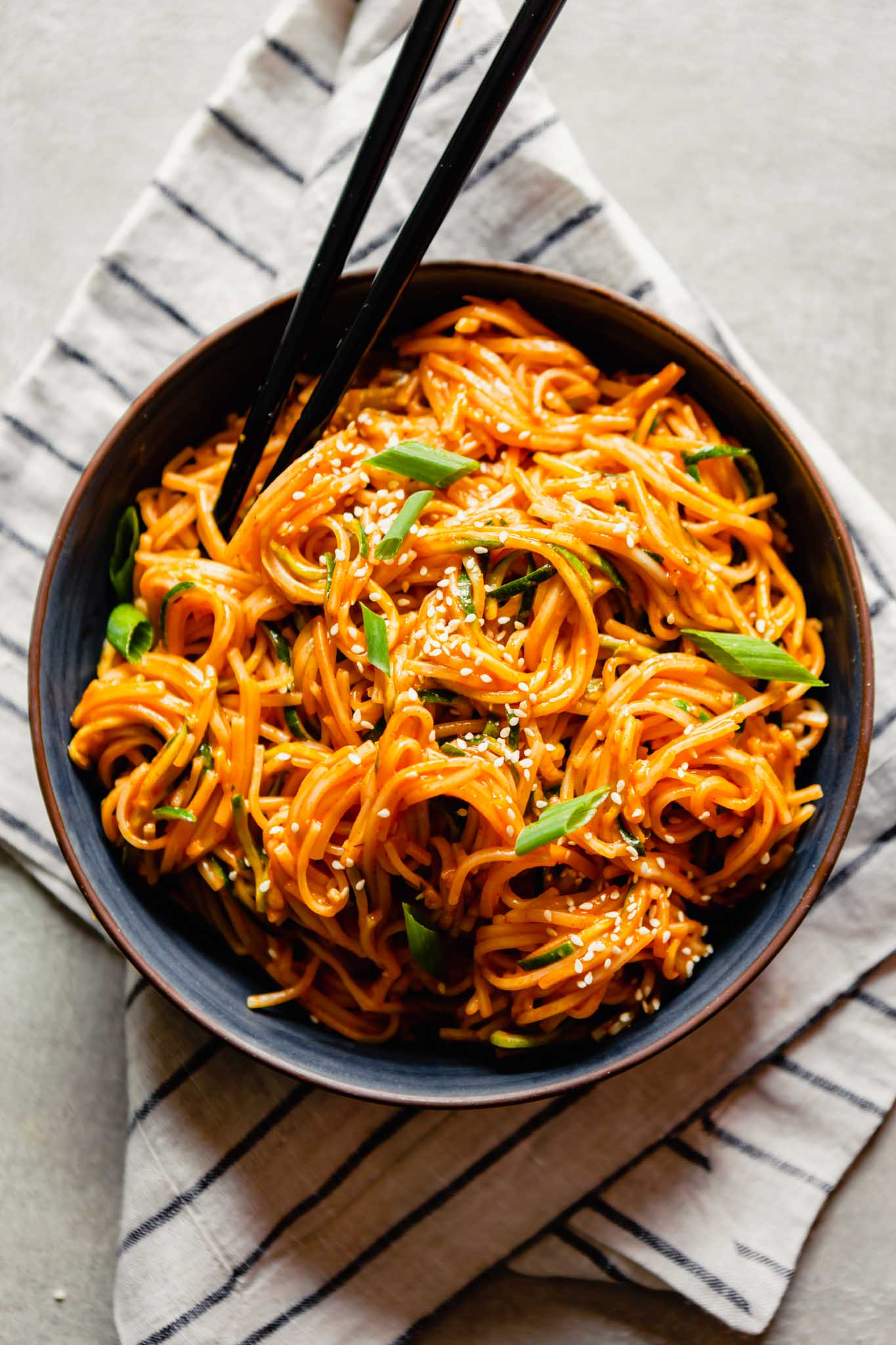 Overhead image of bright orange noodles with gochujang sauce in a dark blue bowl set on a striped napkin.