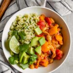 Overhead image of a while bowl filled with brown rice, a saucy veggie mixture, diced avocado and lime wedges.