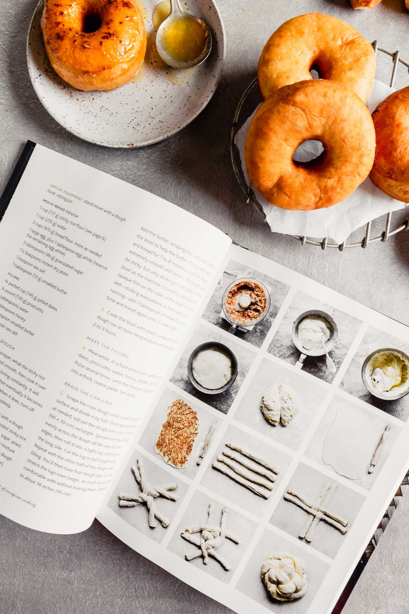 Overhead image of an open cookbook with donuts set around it