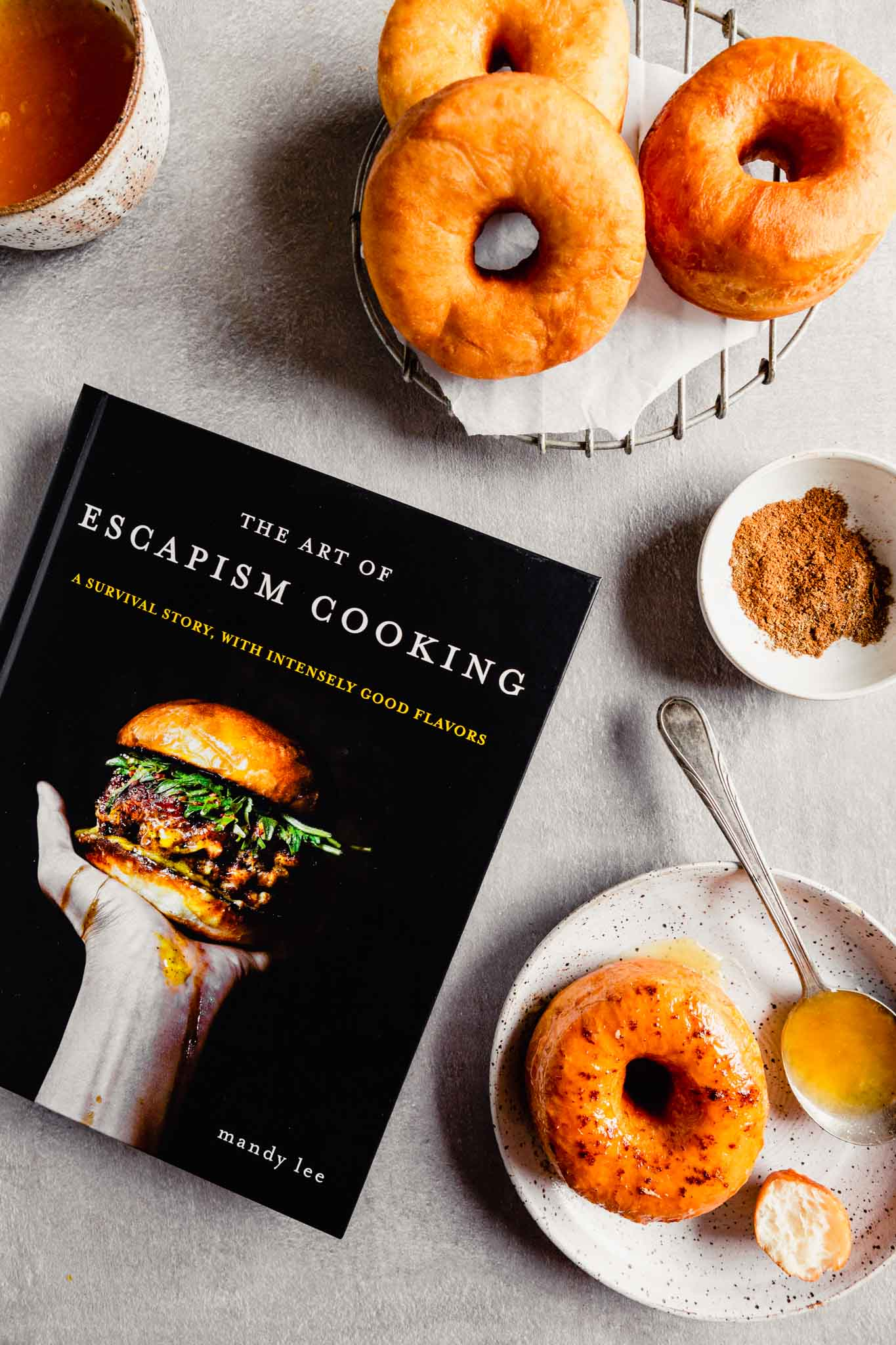 Overhead image of the Art of Escapism Cooking cookbook with donuts spread around it