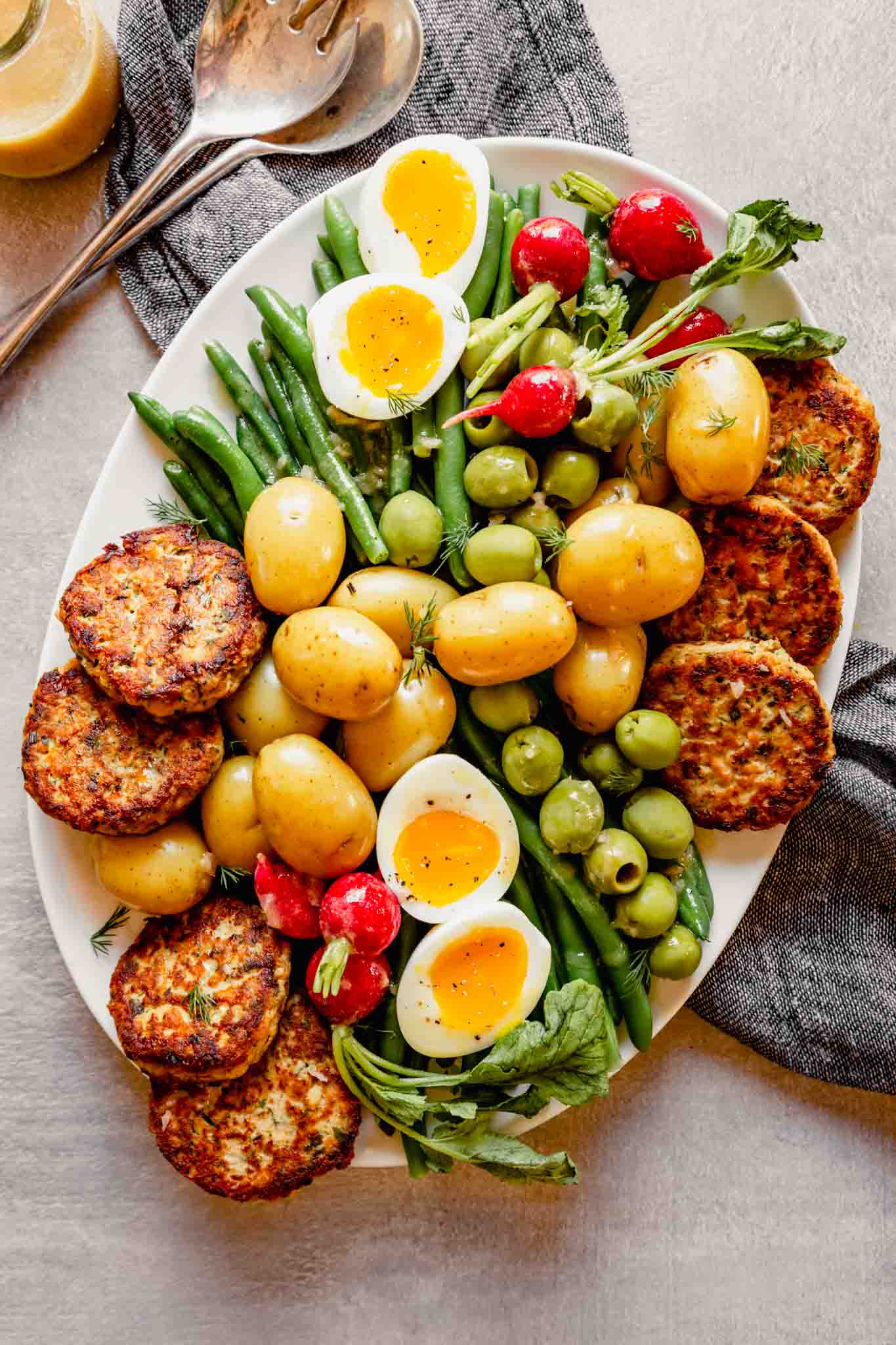 Overhead photo of a nicoise salad on a white oval plate with dressing and serving utensils off to the side
