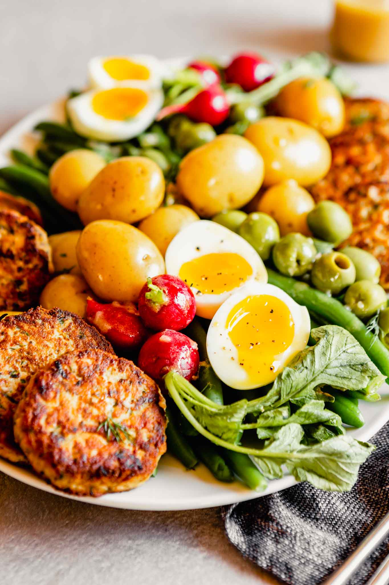 Side angle of a nicoise salad on a white oval plate. Focused on soft boiled eggs and salmon patties.